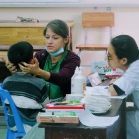 A local child gets a medical check during an outreach from an intern doing her Nursing internship in Vietnam.